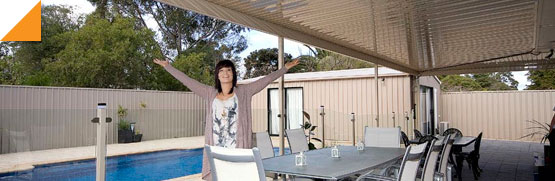 lady standing under a verandah by a pool